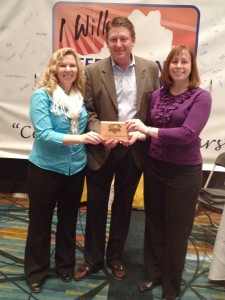 Bryna Dunn and Carrie Webster of Moseley Architects receive a plaque from Mike Baum of Keep Virginia Beautiful.